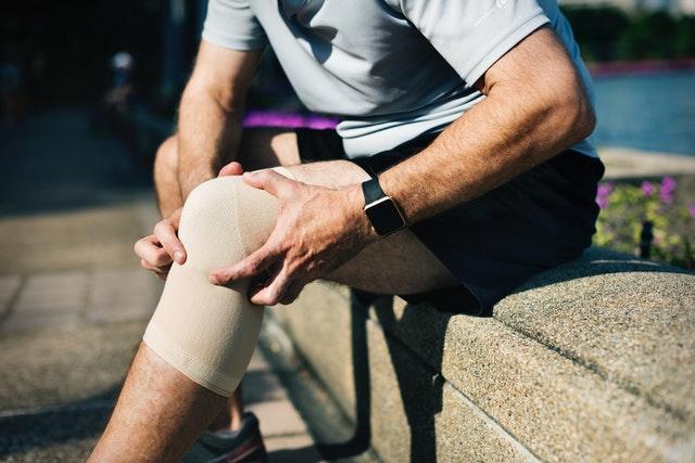 Muž, ktorý si drží obviazané koleno.jpg