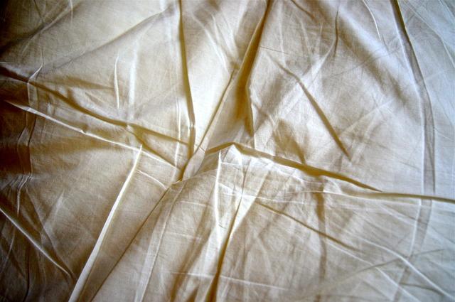 Detail na pokrčenú bielu plachtu na posteli.jpg