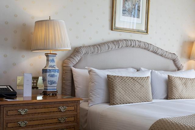 Manželská posteľ s hnedým čalúneným čelom a vankúšmi.jpg