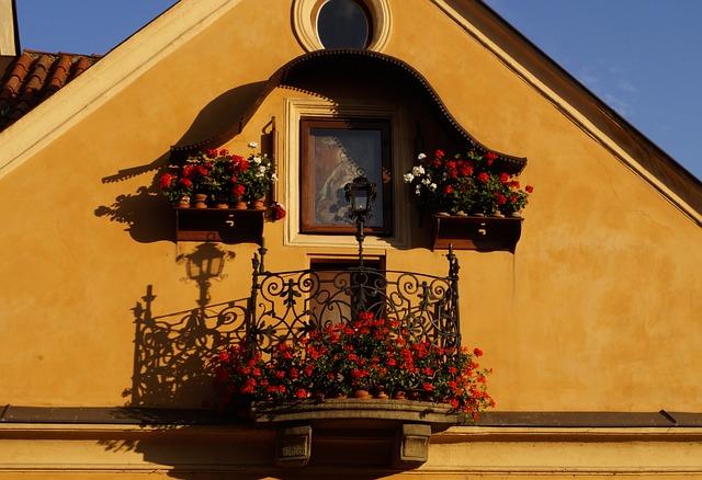 Maličký balkón na oranžovom dome s červenými muškátmi.jpg