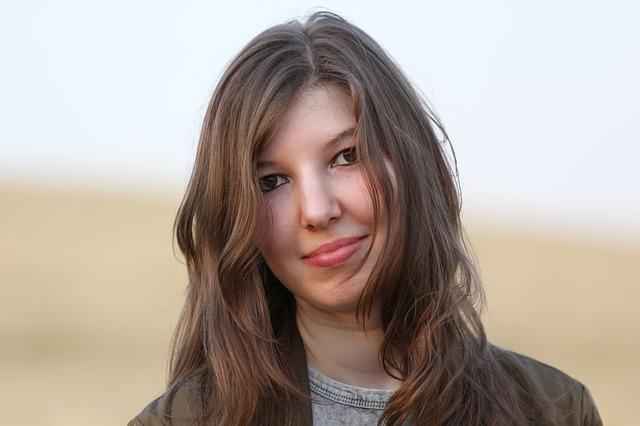 Žena s hnedými vlasmi sa usmieva