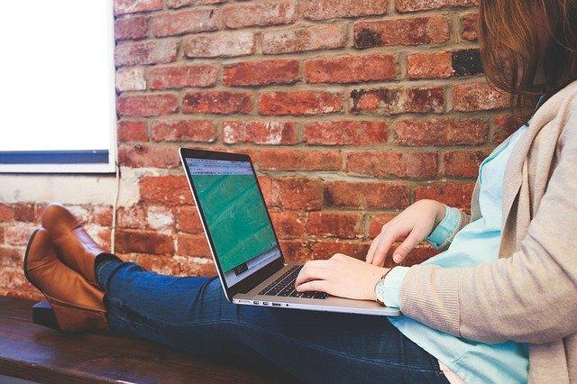 Žena v svetri sedí pri okne a pracuje na notebooku