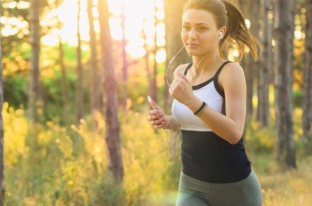 Žena so slúchadlami beží v lese